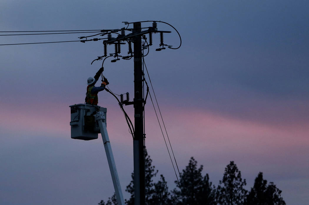 In this Nov. 26, 2018, file photo, a Pacific Gas & Electric lineman works to repair a power lin ...