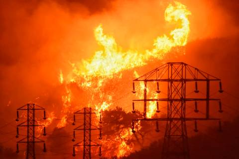 In this Dec. 16, 2017, flames burn near power lines in Sycamore Canyon near West Mountain Drive ...