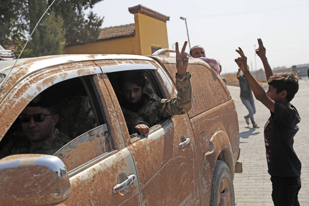 Members of Turkey-backed Syrian National Army (former FSA) flash the V-sign as they drive back ...
