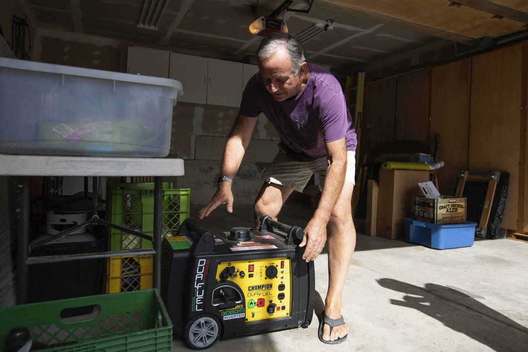 Joe Wilson pulls his generator out in the garage of his home, which is in an area that is expec ...