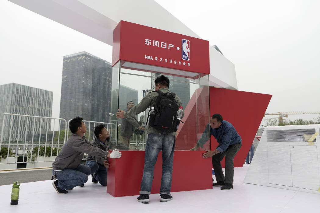 Workers dismantle signage for an NBA fan event scheduled to be held on Wednesday night at the S ...