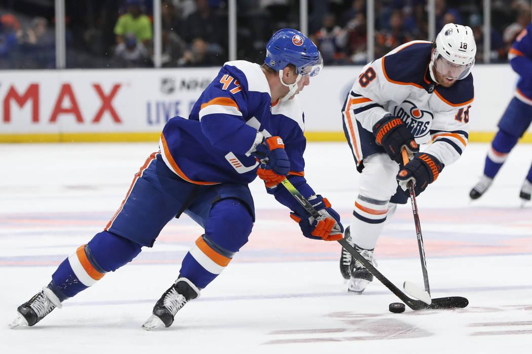Edmonton Oilers left wing James Neal (18) defends against New York Islanders center Leo Komarov ...