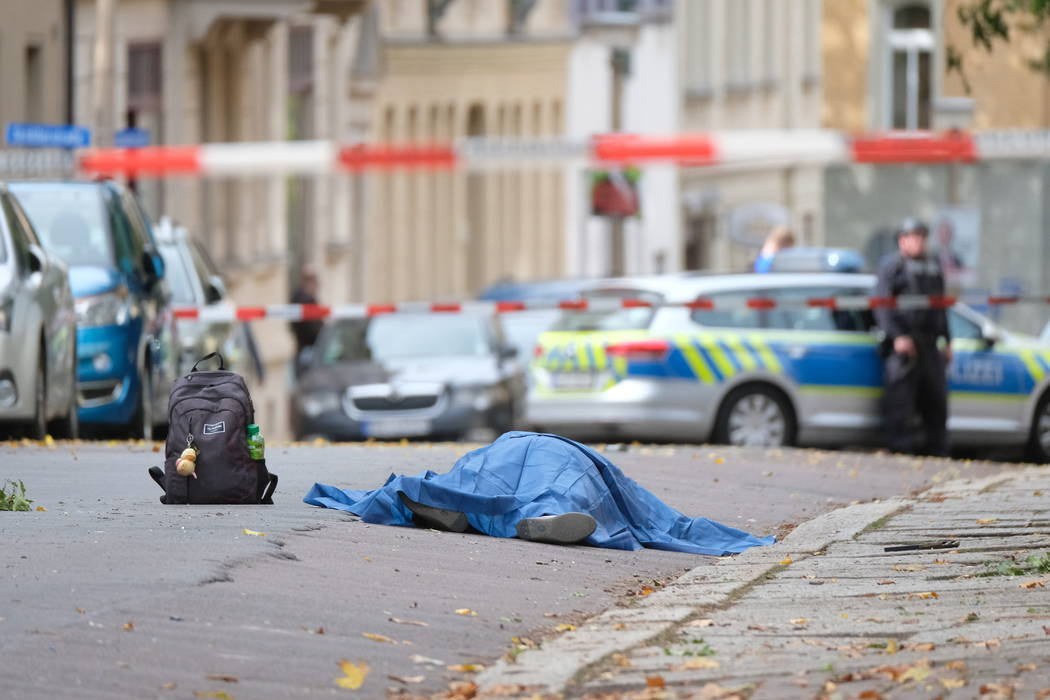 A body lies on a road in Halle, Germany, Wednesday, Oct. 9, 2019 after a shooting incident. A g ...