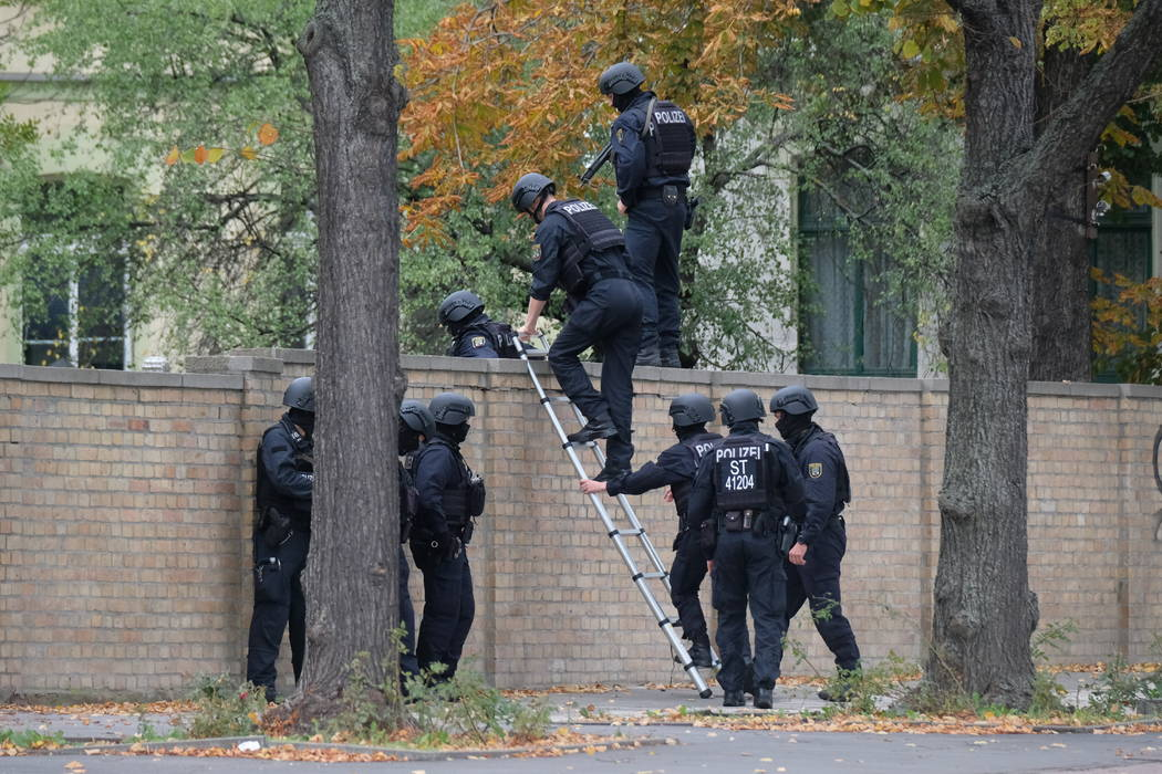 Police officers cross a wall at a crime scene in Halle, Germany, Wednesday, Oct. 9, 2019 after ...