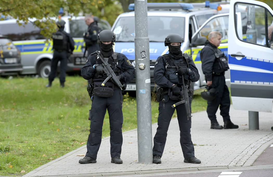 Police officers block a road in Halle, Germany, Wednesday, Oct. 9, 2019. One or more gunmen fir ...