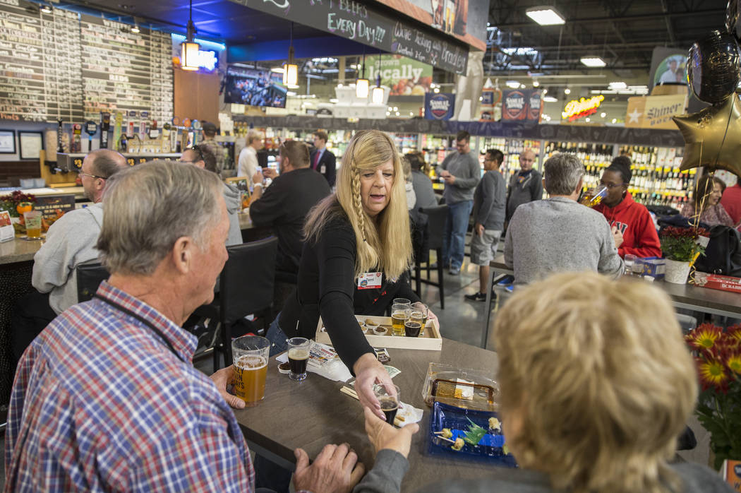 Bartender Terri Wirthlin, middle, hands out beer samples at Social Hour Beer and Wine Bar on Th ...