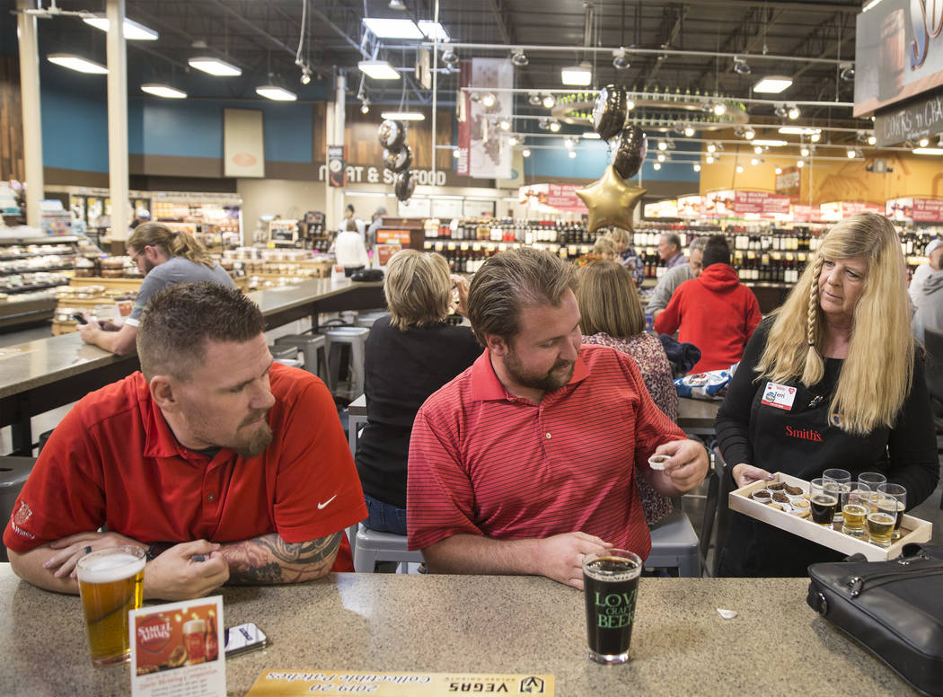 Bartender Terri Wirthlin, right, hands out beer samples to Patrick Shearer, middle, and Donnie ...