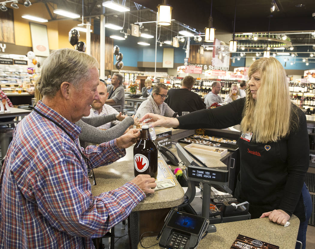 Bartender Terri Wirthlin, right, serves Dave Hicks a growler of beer at Social Hour Beer and Wi ...