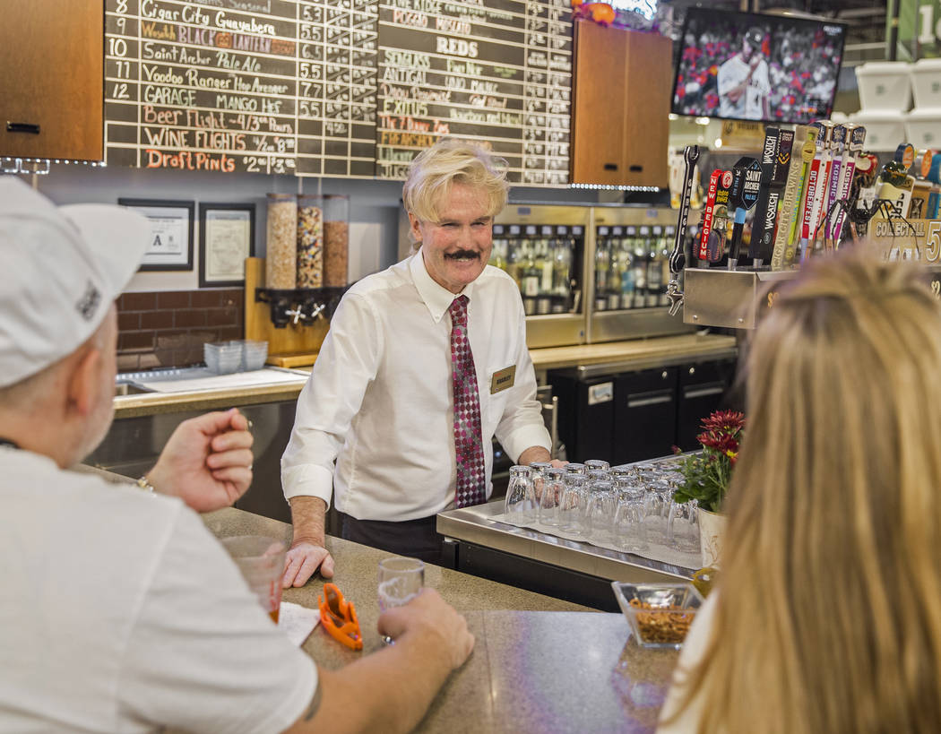 Wine steward Bradley Pugh, middle, talks with patrons at Social Hour Beer and Wine Bar on Thurs ...