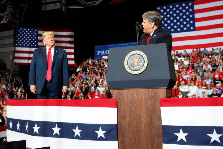 President Donald Trump listens Fox News' Sean Hannity speak during a rally. (AP Photo/Carolyn K ...