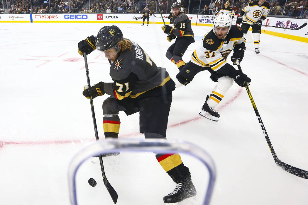 Golden Knights' William Karlsson (71) moves the puck in front of Boston Bruins' Patrice Bergero ...