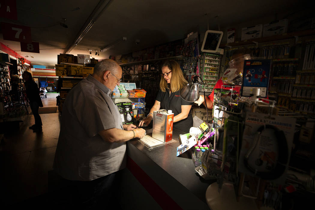 Tom Hyde, left, buys a can of fuel for his Coleman camp stove from Kim Scheffer at a Village Tr ...