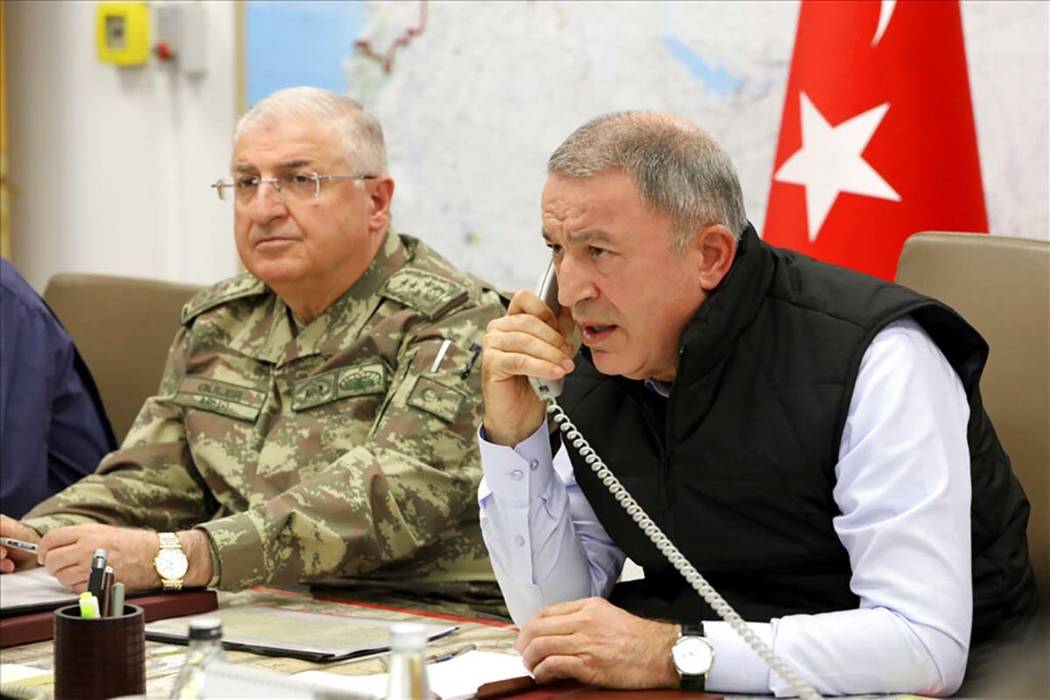 Turkey's Defense Minister Hulusi Akar, right, speaks on the phone alongside Chief of the Genera ...