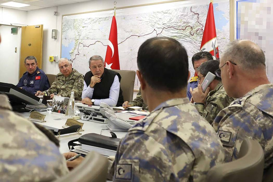In this photo taken late Wednesday, Oct. 9, 2019, Turkey's Defence Minister Hulusi Akar, center ...