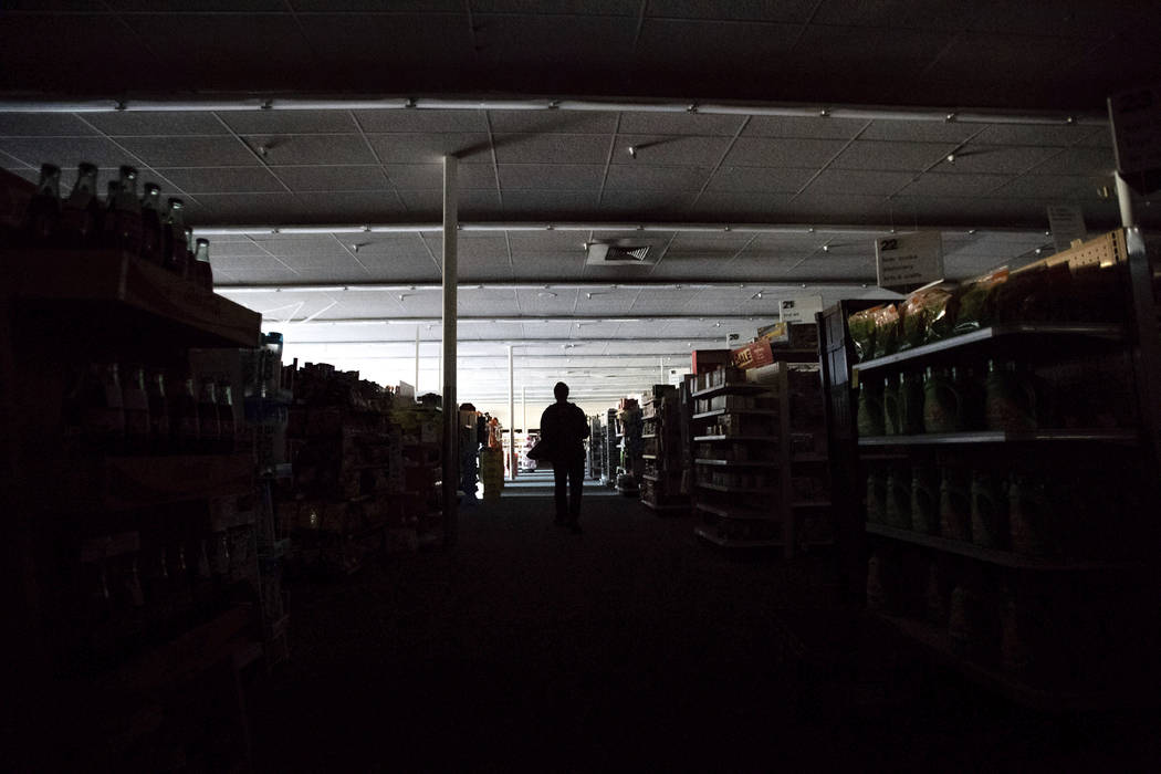 Shift supervisor James Quinn walks through a darkened CVS Pharmacy as downtown Sonoma, Calif., ...