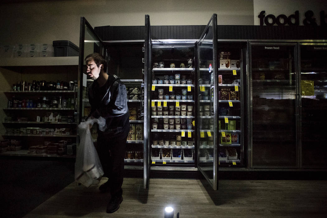CVS Pharmacy shift supervisor James Quinn throws out ice cream from darkened freezers as downto ...
