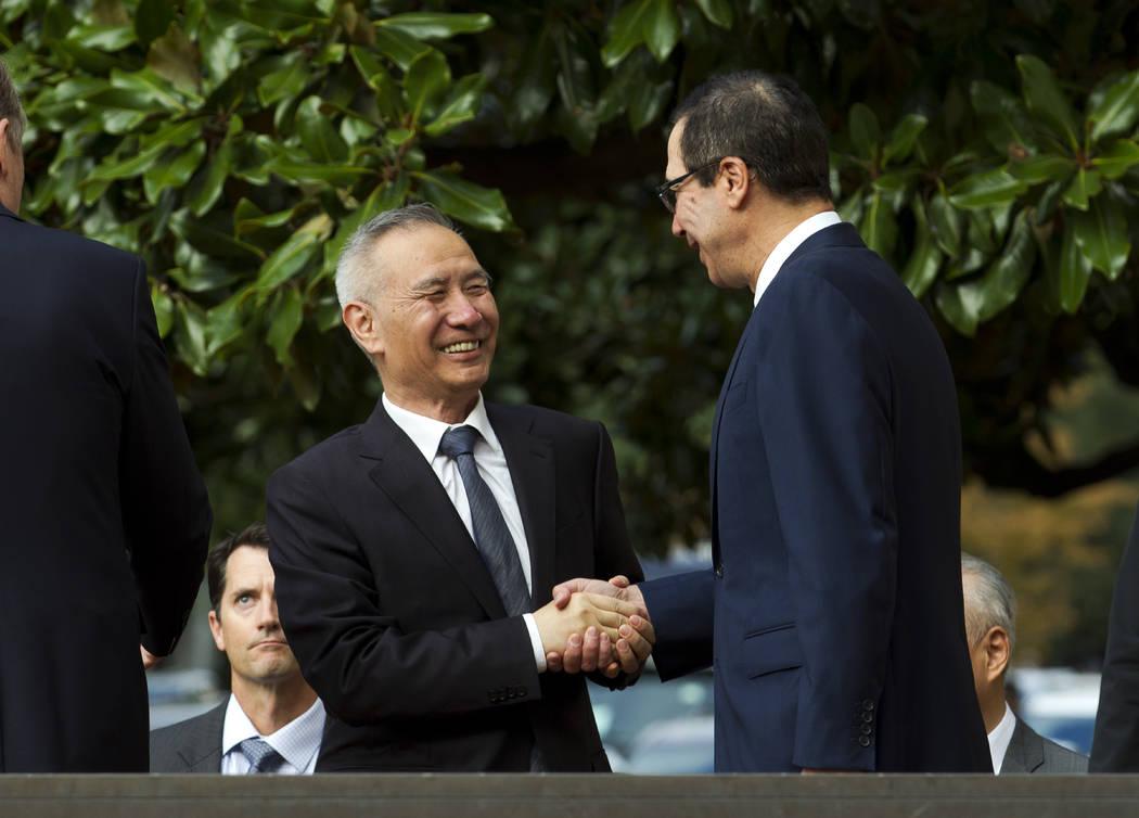 Chinese Vice Premier Liu He shake hands with Treasury Secretary Steven Mnuchin, as he arrives f ...