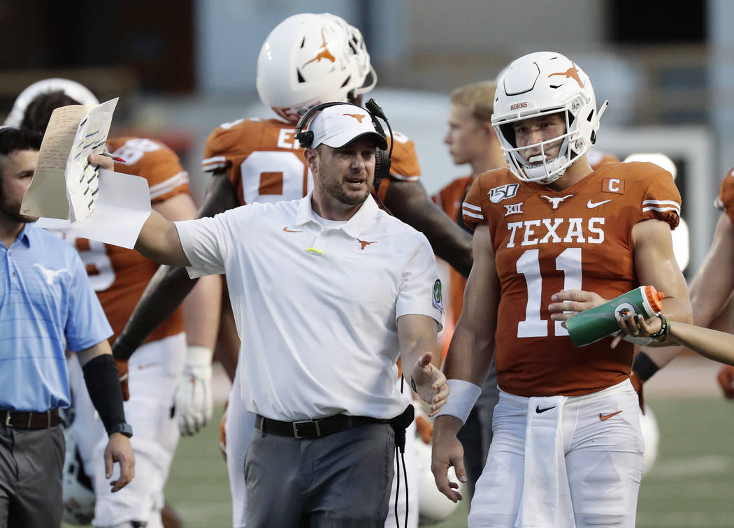 Texas head coach Tom Herman, left, and Texas quarterback Sam Ehlinger (11) during the first hal ...