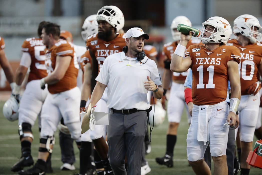 Texas head coach Tom Herman, center, and Texas quarterback Sam Ehlinger (11) during the first h ...