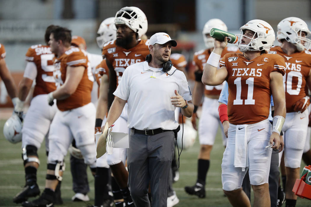 Texas head coach Tom Herman, center, and Texas quarterback Sam Ehlinger (11) during the first h ...
