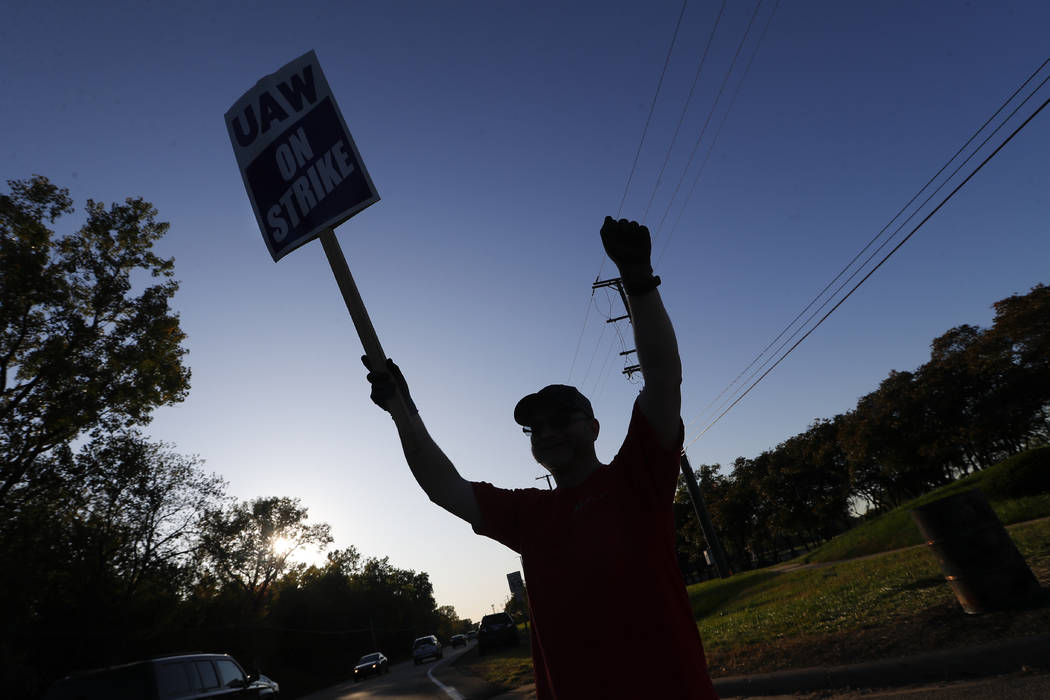 A member of the United Auto Workers cheers on honking cars as he walks the picket line at the G ...