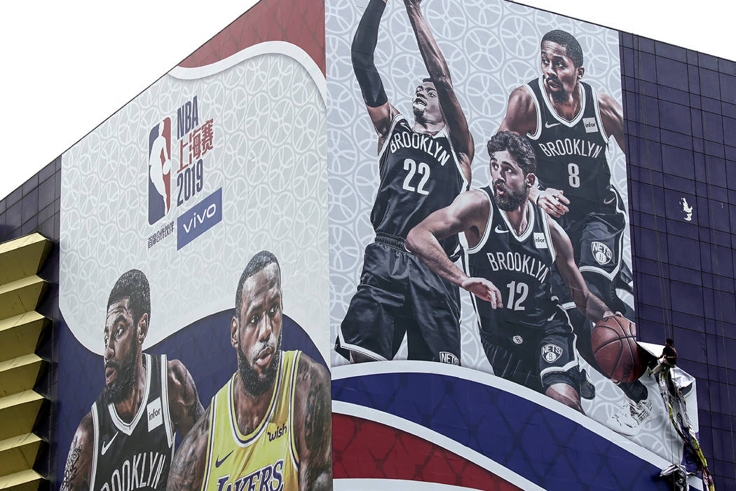 A worker takes down a billboard advertising an NBA preseason basketball game on Thursday betwee ...