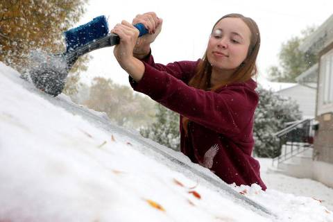MaKenzie Gregory scrapes ice off her vehicle's front windshield as snow continues to fall in Sc ...