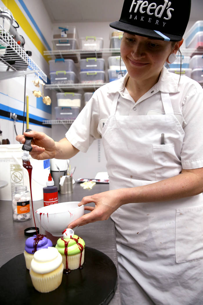 Brittnee Klinger, a cake decorator at Freed's Bakery in Las Vegas covers cupcakes with fake blo ...