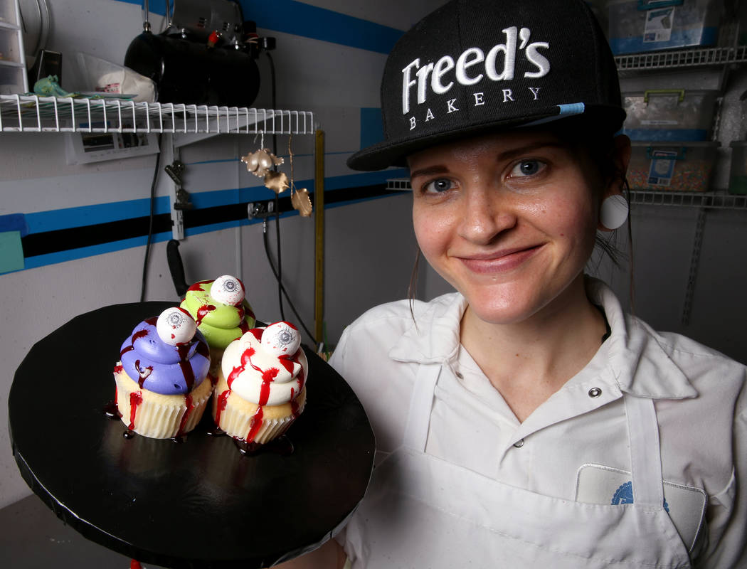 Brittnee Klinger, a cake decorator at Freed's Bakery in Las Vegas shows cupcakes with fake bloo ...