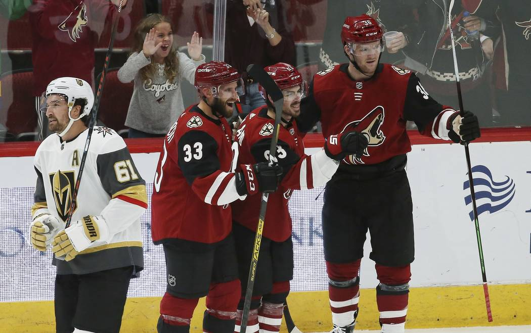 Arizona Coyotes right wing Conor Garland, second from right, celebrates his goal with Coyotes d ...
