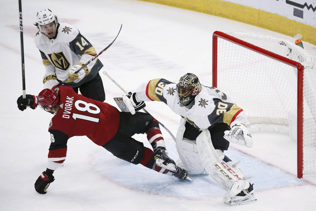 Arizona Coyotes left wing Christian Dvorak (18) gets clobbered by Vegas Golden Knights goaltend ...