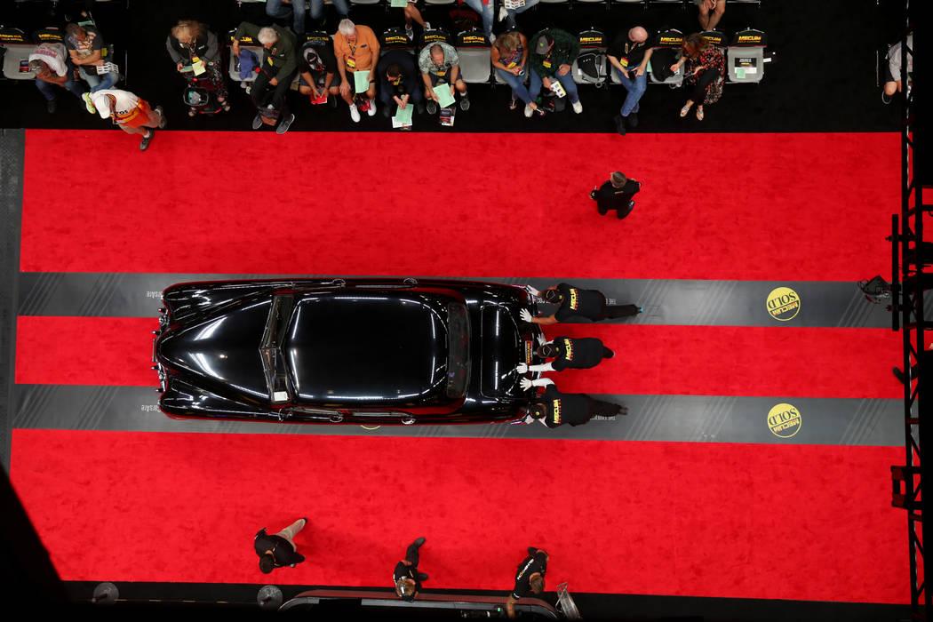Workers push a car on the auction block during Mecum Las Vegas auction at the Las Vegas Convent ...