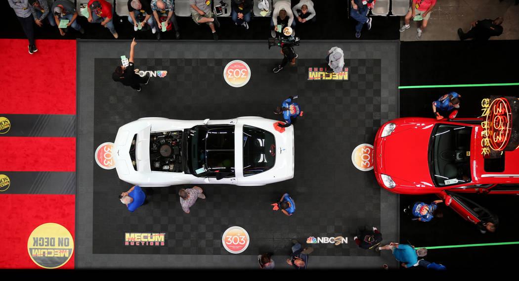 Workers prepare cars for the auction block during Mecum Las Vegas auction at the Las Vegas Conv ...
