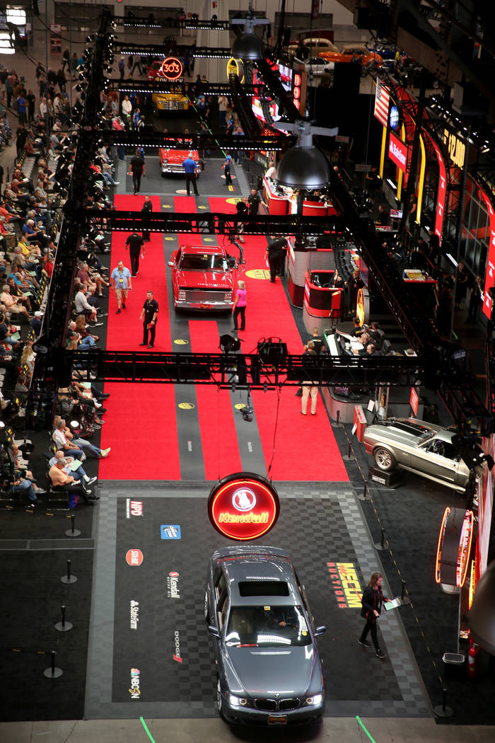 Workers push cars on the auction block during Mecum Las Vegas auction at the Las Vegas Conventi ...