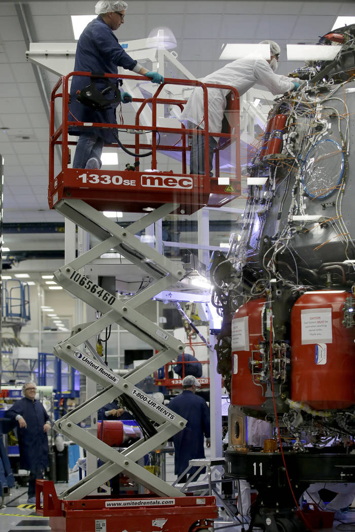SpaceX employees work on the Crew Dragon spacecraft that will take astronauts to and from the I ...