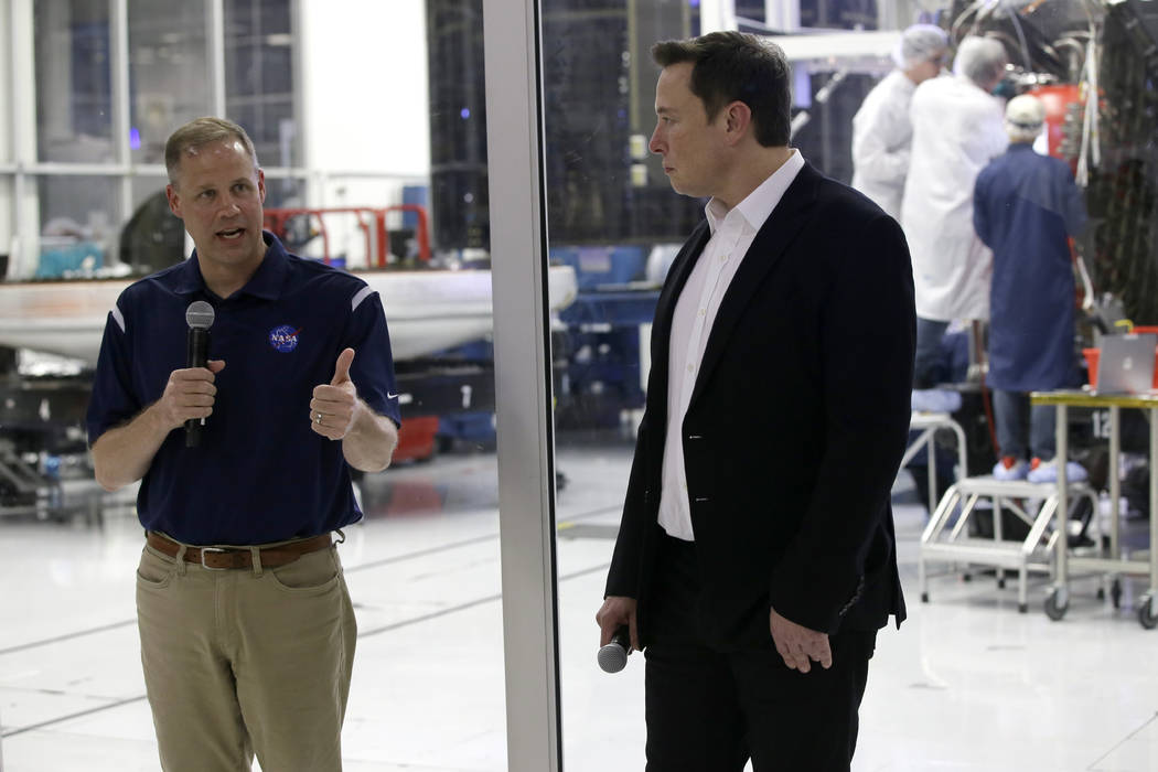 NASA Administrator Jim Bridenstine, left, talks with SpaceX chief engineer Elon Musk, right, in ...