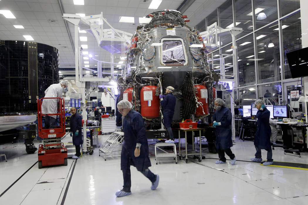 SpaceX employees work on the Crew Dragon spacecraft that will astronauts to and from the Intern ...