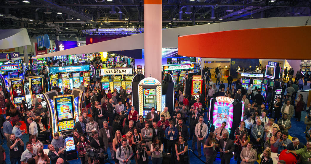 A crowd gathers at the IGT's booth as gameshow host Drew Carey leads the world debut of three I ...