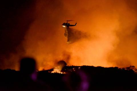 A helicopter drops water on a brushfire in the Santa Monica Mountains in Newbury Park, Calif., ...