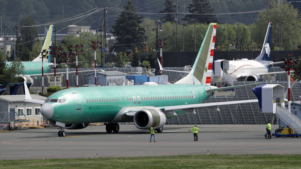 FILE - In this Wednesday, May 8, 2019 file photo, workers stand near a Boeing 737 MAX 8 jetline ...