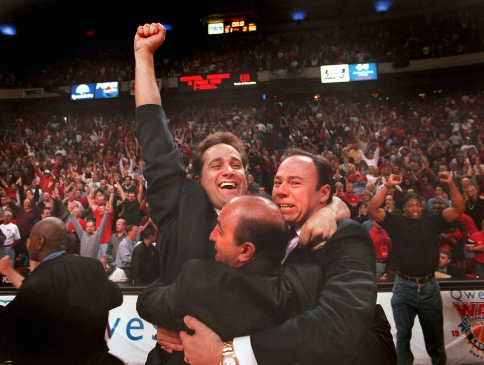 UNLV basketball coach Bill Bayno and his coaching staff celebrate the Rebels 56-51 victory ove ...