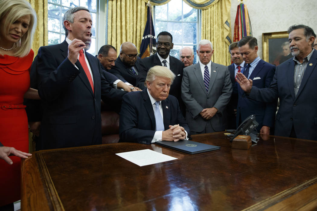 In a Sept. 1, 2017, file photo, religious leaders pray with President Donald Trump after he sig ...