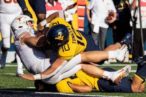 West Virginia linebacker Dylan Tonkery (10) tackles Texas quarterback Sam Ehlinger, left, who c ...