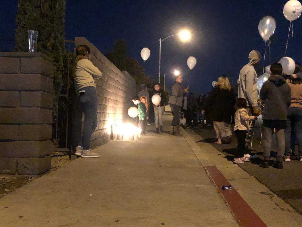 Nearly a hundred mourners gathered on Friday, Oct. 11, 2019, outside the Viridian Apartments, 4 ...