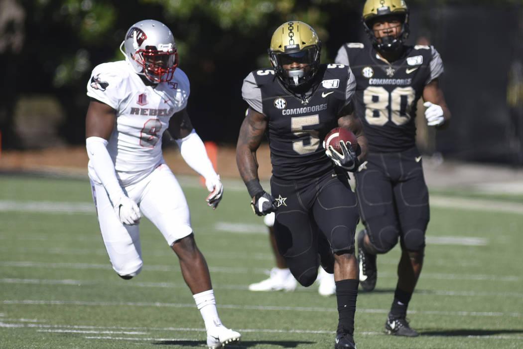 Vanderbilt running back Ke'Shawn Vaughn runs with the ball past UNLV linebacker Rayshad Jackson ...