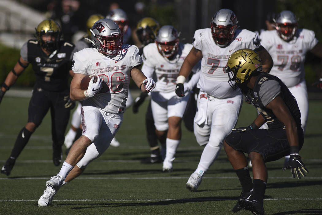 UNLV running back Chad Maygar (38) runs next to Vanderbilt defender Brendon Harris (13) in the ...