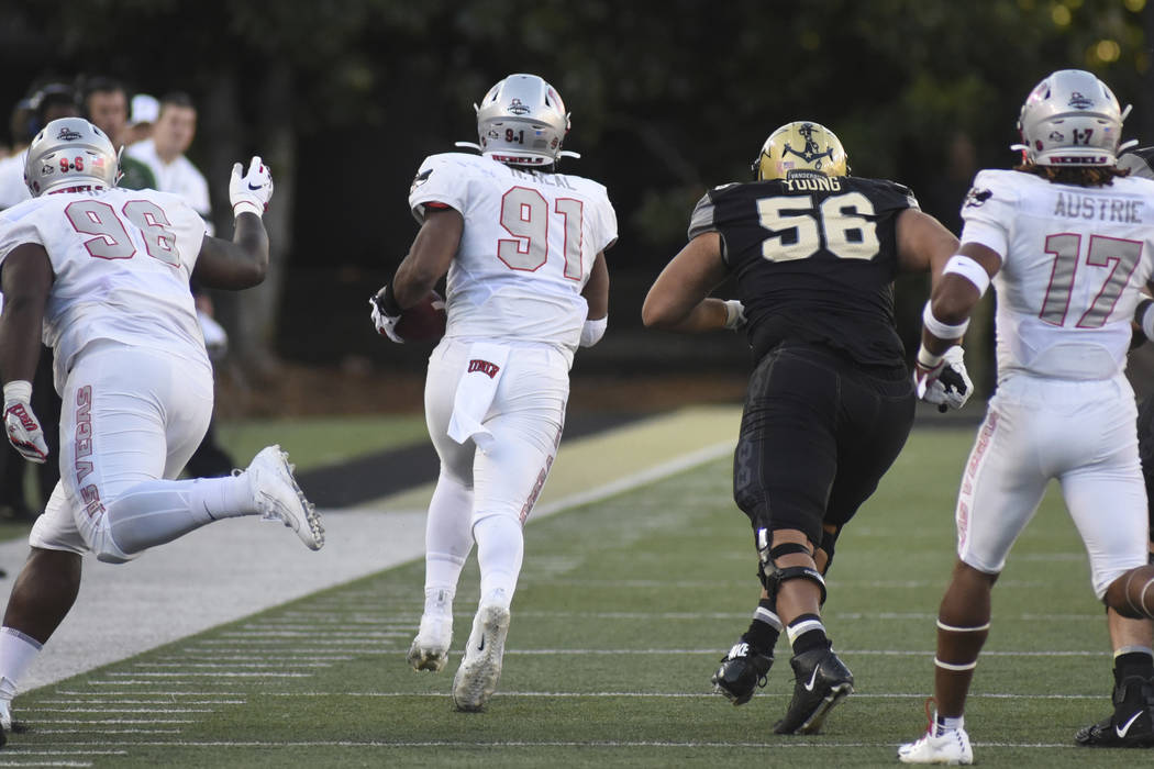 UNLV defensive end Nate Neal (91) returns a fumble past Vanderbilt lineman Saige Young (56) in ...