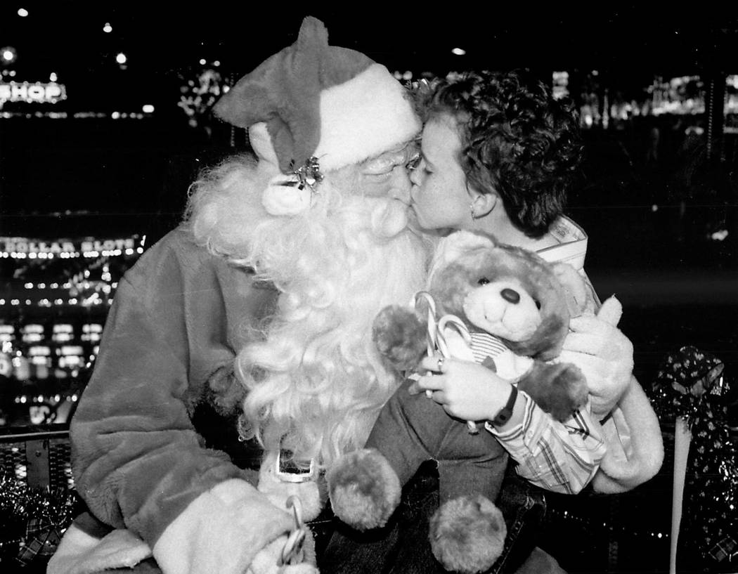 Carrie Maness, 9, of Forest Virginia, plants a kiss on Santa's nose on the midway at Circus Cir ...