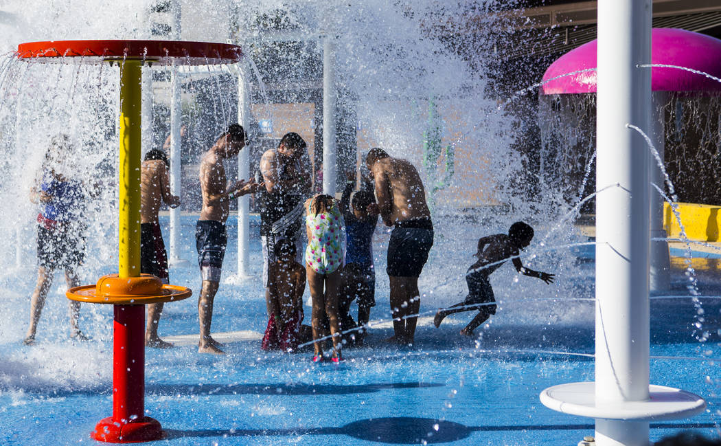 Hotel guests enjoy a water feature at the pool area at Circus Circus in Las Vegas on Friday, Ju ...