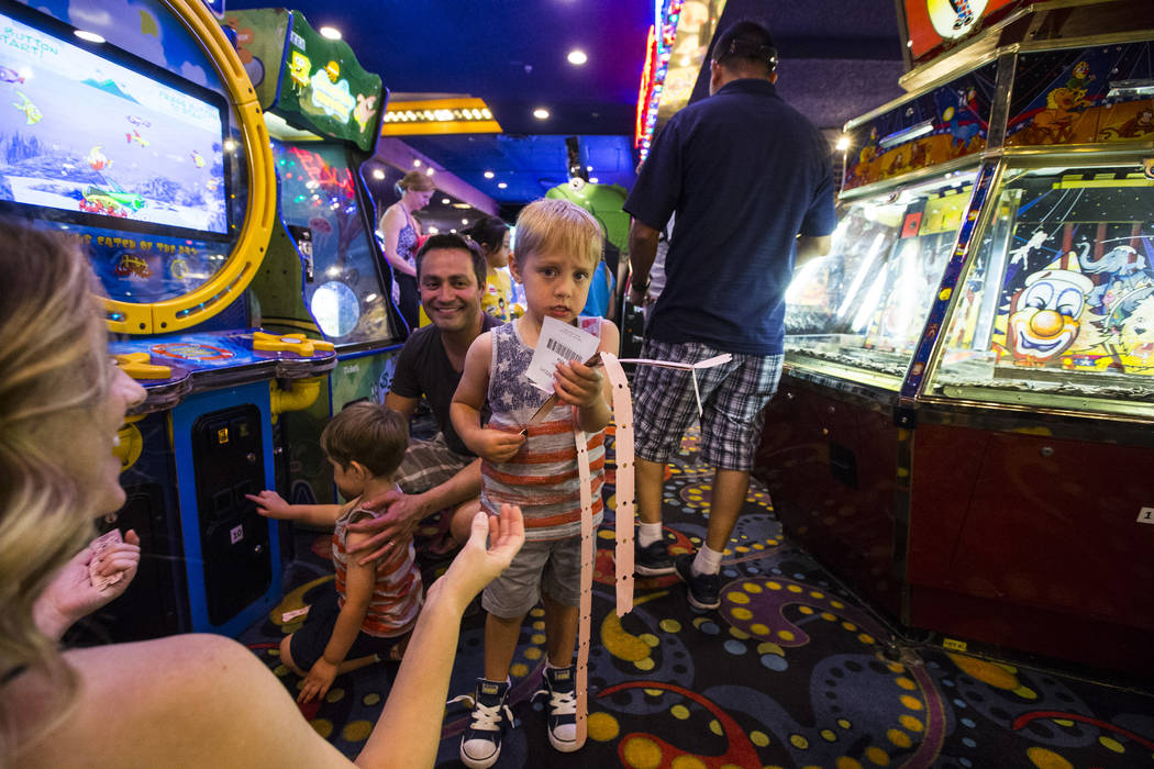 Four-year-old Emil Borrego holds his tickets as his mother Leslie Daniel, left, and father Reub ...